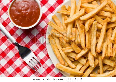 top view of french fries on plate with ketchup on checkered tablecloth