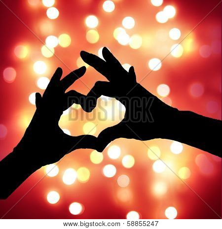 yellow bokeh, defocused lights with heart hands silhouette - good for christmas or valentine's day