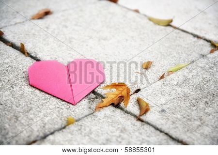 an origami heart on concrete paver blocks good for valentine's day or fall