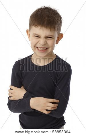 Little boy standing arms crossed showing his teeth, snarling, looking at camera.