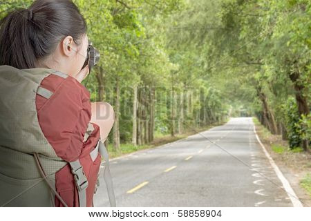 Young backpacker travel and take picture on a road with forest.