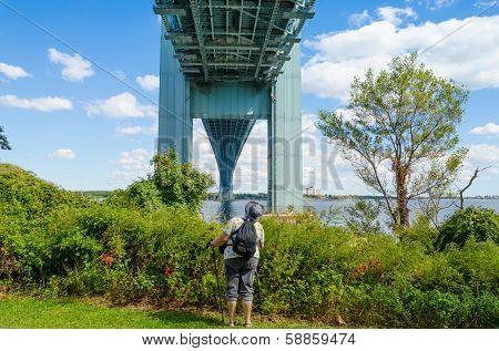 Senior tourist looking at Verrazano-Narrows Bridge, NYC - view from Staten Island