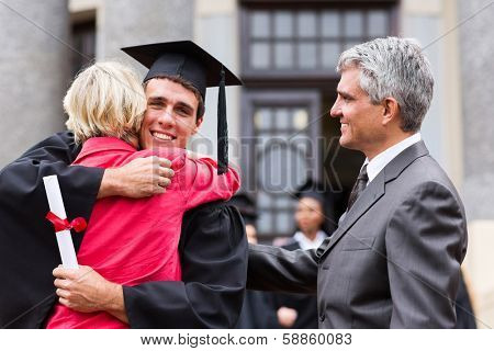 happy male graduate hugging his mother at graduation ceremony