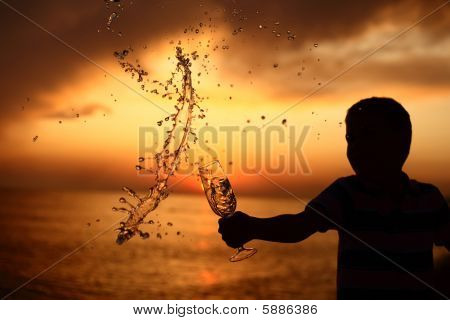 Silhouette Of Boy Splashes Out Drink From Glass On Sea Sunset