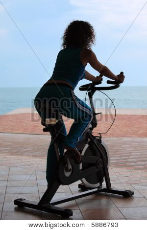 Silhouette Of Girl On Bicycle Training Apparatus Outdoor