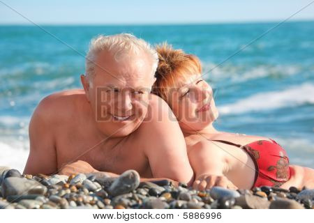 Happy Aged Pair Lie On Pebble Beach