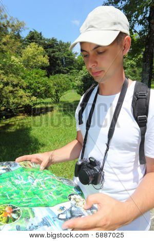 Photographer Looks On Map In Sochi Arboretum