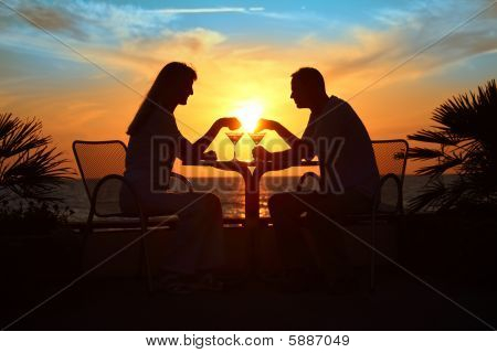 Female And Man  On Sunset Sit At Table With Two Glasses