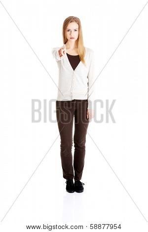 Beautiful casual woman pointing on you and warning or accusing of sth. Isolated on white.