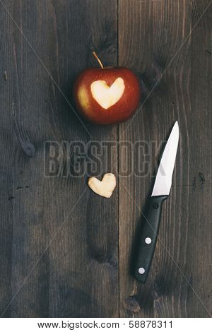 apple with piece in heart shape and knife