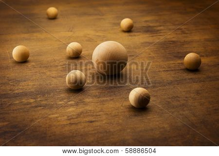 Wooden spheres on a grungy old desk, representing a planetary or atomic particle formation.