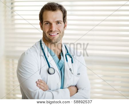 Portrait of confident male doctor with arms crossed standing at clinic