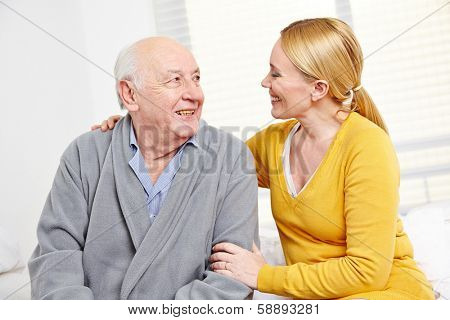 Woman and old senior man in retirement home smiling at each other