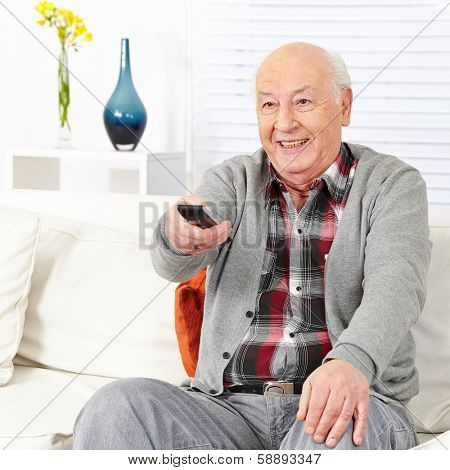 Happy senior citizen man watching TV with remote control