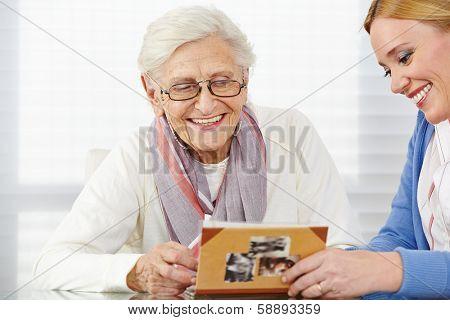 Happy senior woman watching photo album with eldercare nurse