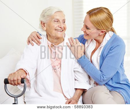 Happy senior citizen woman at home looking at her daughter