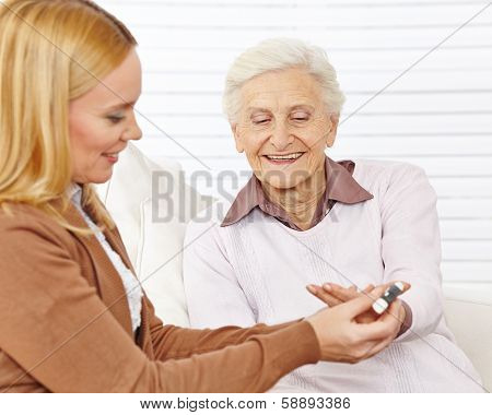 Woman doing a blood sugar measurement for senior citizen with diabetes