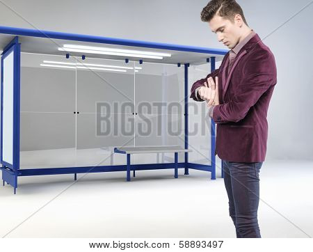 A young man at a bus stop checking his watch