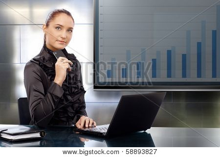 Young businesswoman sitting at meetingroom, doing presentation of business results, sitting front of LCd display.