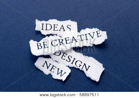 Roughly cut slips of paper with creativity concepts such as ideas, be creative, design, new