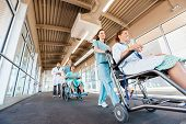 pic of wheelchair  - Low angle view of female nurses pushing patients on wheelchairs with doctor walking at corridor in hospital - JPG