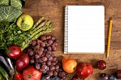 stock photo of plum fruit  - studio photography of open blank ring bound notebook surrounded by a fresh vegetables and pencil on old wooden table - JPG