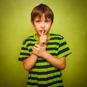teenager boy holding finger to his mouth silence requested quiet