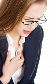 Beautiful business woman touching her chest, feeling unwell. Heart attach, health concept. Isolated