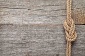 stock photo of ship  - Ship rope knot on old wooden texture background - JPG
