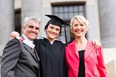 stock photo of white gown  - beautiful young female graduate with parents at ceremony - JPG