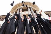 stock photo of graduation  - group of happy graduates throwing graduation hats in the air celebrating - JPG