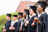 stock photo of graduation gown  - group of multiracial university graduates at graduation ceremony - JPG
