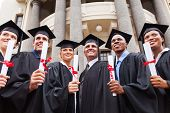 stock photo of graduation gown  - group of multicultural graduates standing outdoors with dean - JPG