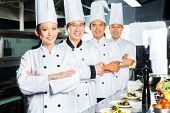 picture of chinese restaurant  - Asian Indonesian and Chinese chefs along with other cooks in restaurant or hotel commercial kitchen cooking - JPG