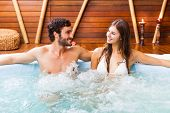 stock photo of tub  - Happy couple relaxing in a hot tub - JPG