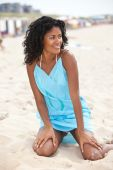 stock photo of black curly hair  - Beautiful brazilian girl sitting in the sand on the beach - JPG