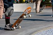 Skateboarders Prepare To Drop In At Skateboard Park Bowls