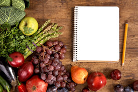 pic of nutrients  - studio photography of open blank ring bound notebook surrounded by a fresh vegetables and pencil on old wooden table - JPG