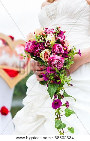 Wedding bride with bridal bouquet and doves outside at garden