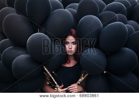 Beautiful girl walking with black balloons