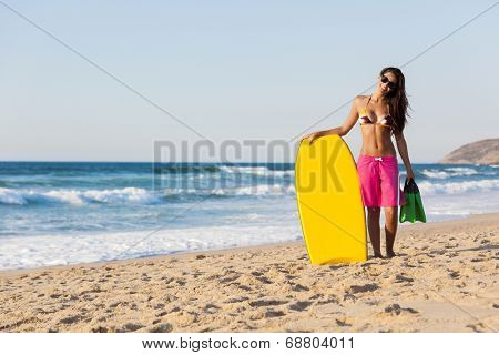 A beautiful girl at the beach with her bodyboard