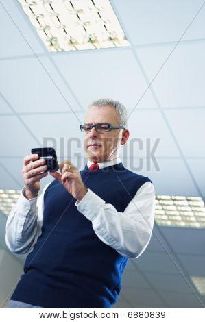 Maduro empresario leyendo e-mails en el teléfono móvil