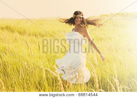 happy smiling woman in boho style clothes run  through the field, sunny summer day, retro colors