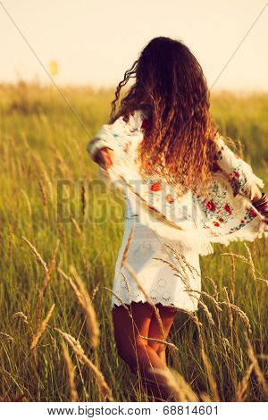 woman wearing boho style clothes run through the grass, hot summer day, retro colors, motion blur