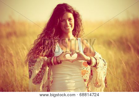 smiling young woman in summer field show heart shape hands sign