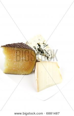 Delicatessen Cheeses On White Porcelain
