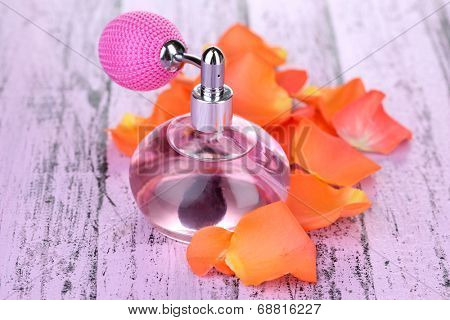 Perfume bottle with petals on table close-up