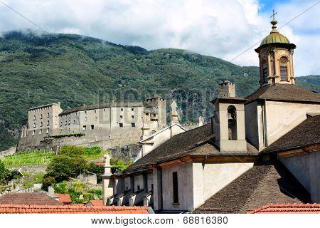 BELLINZONA, SWITZERLAND - July 4, 2014: The Collegiate Church and Castelgrande in Bellinzona, Switzerland. Two of Bellinzonas most famous landmarks and UNESCO World Heritage Site.