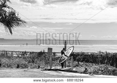 Surfer washing under beach shower