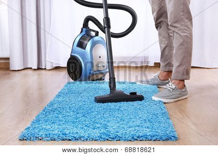 Man doing vacuum cleaning in room